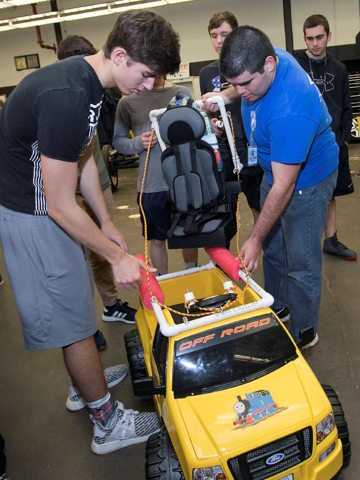 Southington High School student Calvin Gumprecht,  left, and Central Connecticut State University student Cody McQuarrie lower a seat into a modified battery-powered car for one of two special needs children at Southington High School Friday.