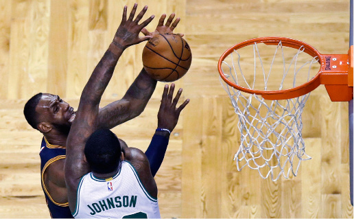 Cleveland Cavaliers forward LeBron James, left, is fouled by Boston Celtics forward Amir Johnson (90) on a drive to the basket during the first quarter of an NBA basketball game in Boston, Wednesday, March 1, 2017. (AP Photo/Charles Krupa)