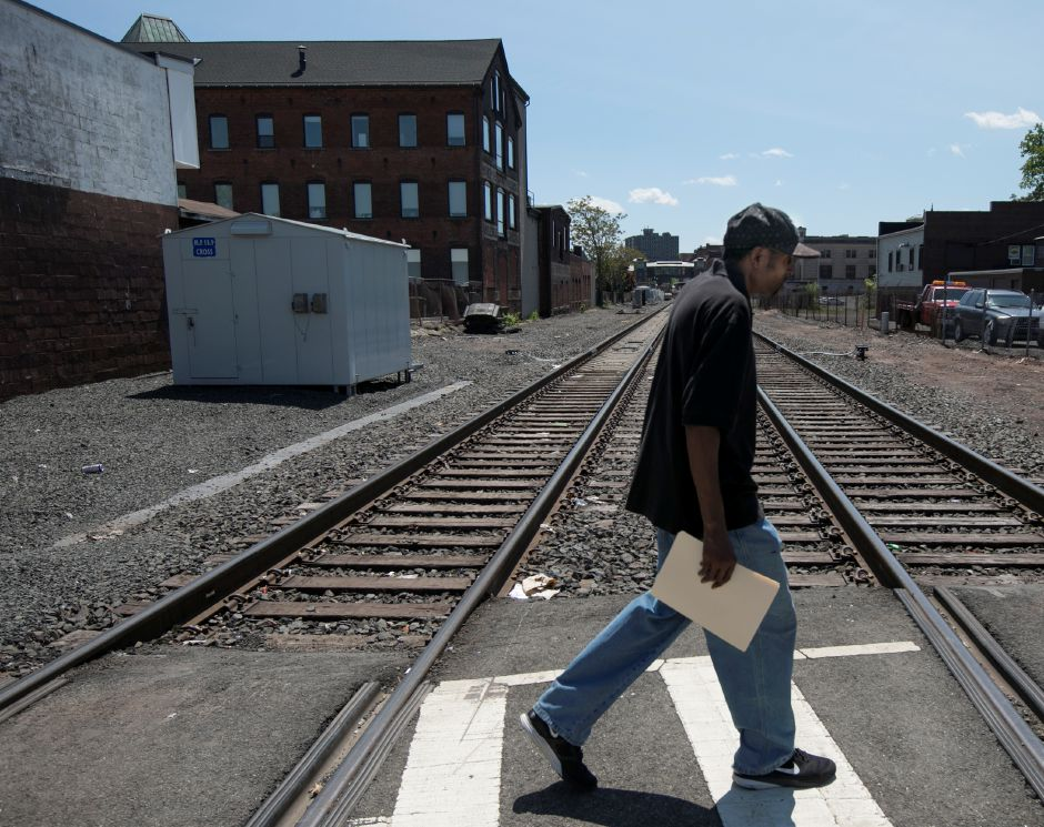 Jeffrey Burts, of Meriden, walks over tracks at the Cross Street rail crossing in Meriden, Wednesday, May 23, 2018. Area residents are being informed of the new CTrail Hartford Line schedule. Dave Zajac, Record-Journal