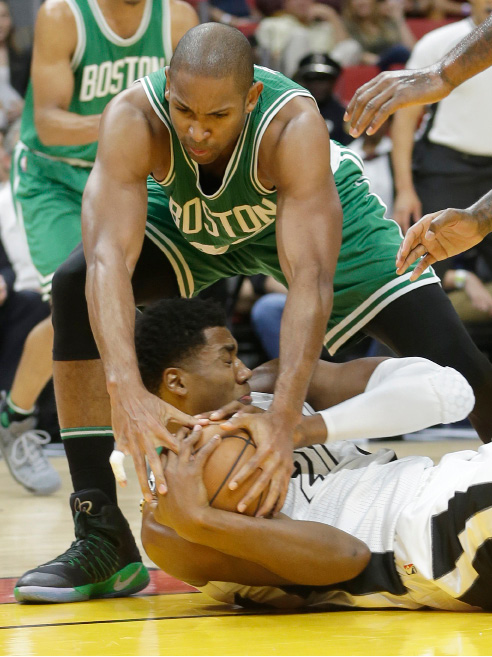 Boston Celtics center Al Horford, top, battles Miami Heat center Hassan Whiteside, bottom, for control of a loose ball in the first half of an NBA basketball game, a jump ball was called, Sunday, Dec. 18, 2016, in Miami. (AP Photo/Alan Diaz)