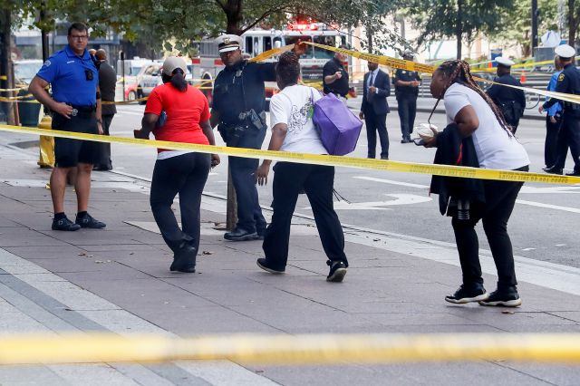 Pedestrians are allowed to exit police cordons as emergency personnel and police work the scene of shooting near Fountain Square, Thursday, Sept. 6, 2018, in downtown Cincinnati. (AP Photo/John Minchillo)