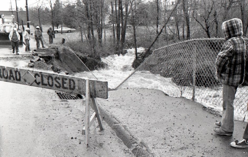 People watch as crews survey flood waters damaging Westfield Road in Meriden, April, 1975.