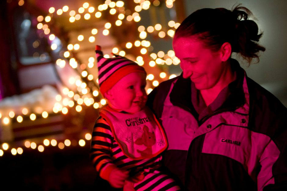 "Kimberly Palmieri, of Southington, holds son Daniel Ames, 8 months, while enjoying ""Christmas in the Village"" in Plantsville, Thursday, December 5, 2013. 