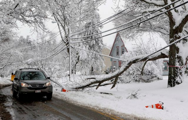 A motorist navigates around a downed limb partially blocking a road and resting on a power line after a snowstorm, Thursday, March 8, 2018, in Northborough, Mass.  The storm produced heavy, wet snow that brought down tree limbs and power lines. (AP Photo/Bill Sikes)
