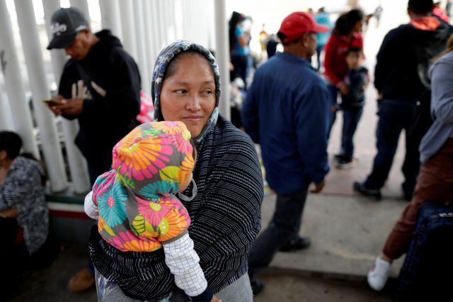 In this June 13, 2018 photo, Maria Rafaela Blancante, of the Mexican state of Michoacan, holds her daughter, Jazmin, as they wait with other families to request political asylum in the United States, across the border in Tijuana, Mexico. The family has waited for two weeks in this Mexican border city, hoping for a chance to escape widespread violence in their home state. (AP Photo/Gregory Bull)