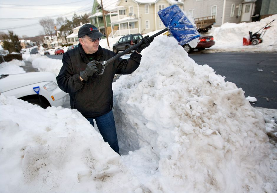 Pat Cronin, of Meriden, digs a passage through a large mound of snow in front of his residence on Hobart St. in Meriden, Wednesday, February 4, 2015. Many are still shoveling out after two storms within a week buried south-central Connecticut under more than 2 feet of snow in some areas. | Dave Zajac / Record-Journal