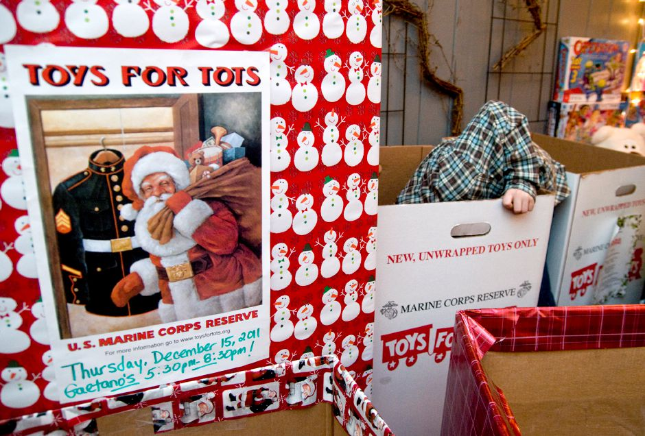 Wallingford resident Sean Fitzsimmons,8, reaches into the bottom of a donation box to grab the last presents as he helps sort donations during the Toys for Tots Party at Gaetano