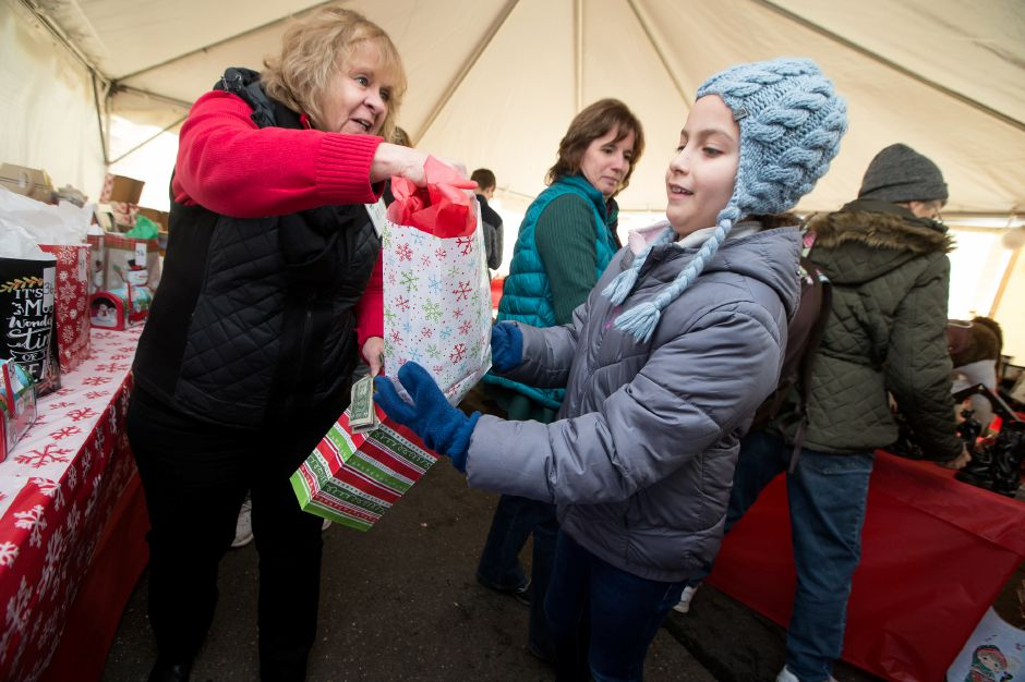 Rei Heitzenrater, 11, of Meriden gets her kids grab bag from Rose Zolnik Saturday during the 27th Annual Franciscan Christmas Fair at the Franciscan Life Center in Meriden November 17, 2018 | Justin Weekes / Special to the Record-Journal