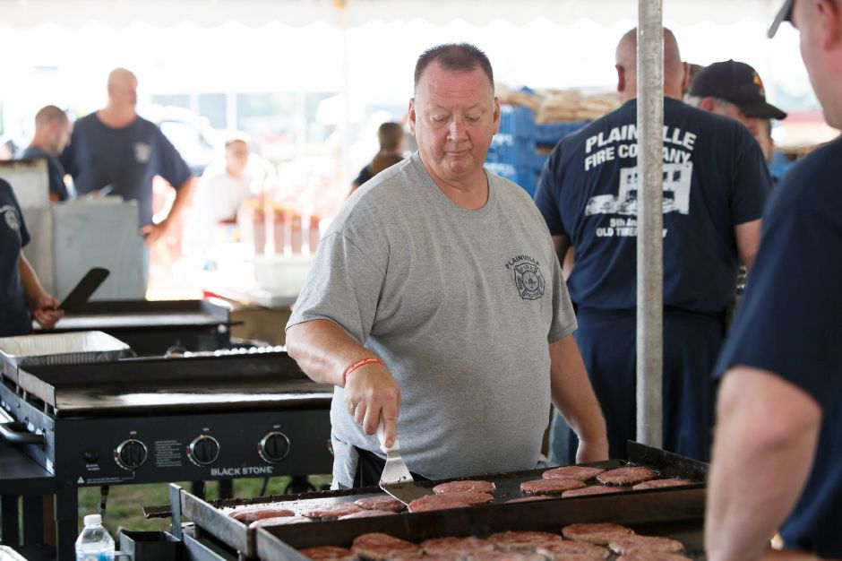 Battalion Chief Andrew Moore cooks burgers in the Plainville Fire Department food tent Friday during the 34th Annual Plainville Balloon Festival at Norton Park in Plainville August 24, 2018 | Justin Weekes / Special to the Record-Journal