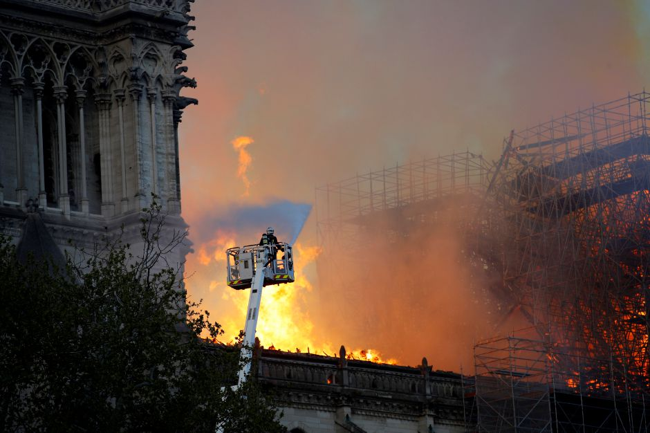A fire fighter uses a hose as Notre Dame cathedral is burning in Paris, Monday, April 15, 2019. A catastrophic fire engulfed the upper reaches of Paris