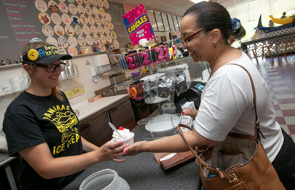 Manager Marissa Klimovich serves up a cherry-vanilla hot fudge coconut sundae with whip cream and cherry for customer Cerise Garrett, of Meriden.