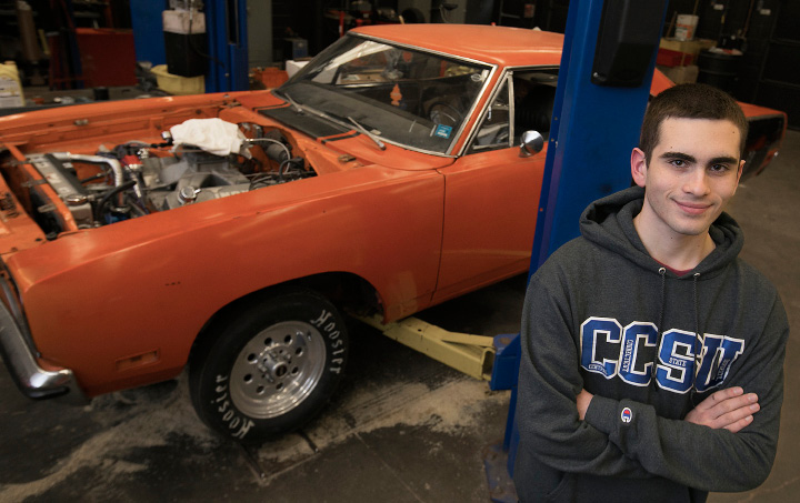 Student Jared Fernandez stands next to a 1971 Roadrunner in a technical education classroom at Southington High School, Friday, March 24, 2017. Fernandez is planning a car show fundraiser in honor of Robert Beeney, a technical education teacher who died in 2015. The car show is Saturday May 13 from 10am-3pm at the Southington Drive-in.  | Dave Zajac, Record-Journal