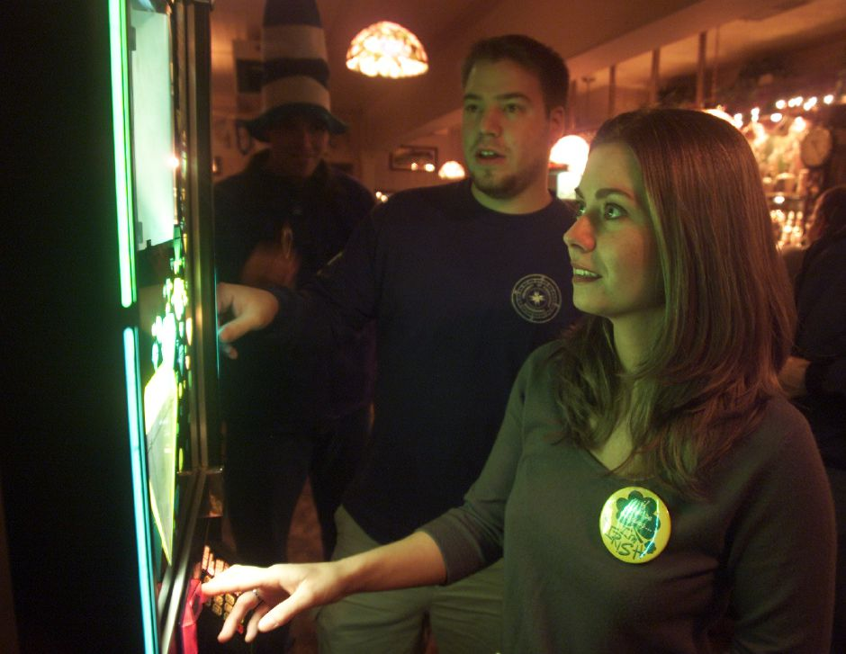 Renee Babineau, right, of Rocky Hill, and her friend David Williams, of Branford, scroll through the musical selections at a jukebox inside Old Dublin in Wallingford. Babineau said she and her friends like making the rounds to the bars in Wallingford because there are many that are close together.