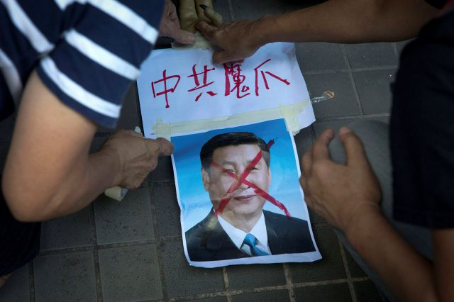 "FILE - In this Saturday, July 1, 2017, file photo, pro-democracy activists paste the words ""Chinese Communist Demon Claws"" on a defaced photo of Chinese President Xi Jinping before attempting to march in protest towards the venue where official ceremonies are held to mark the 20th anniversary of Chinese rule over Hong Kong in Hong Kong. (AP Photo/Ng Han Guan, File)"