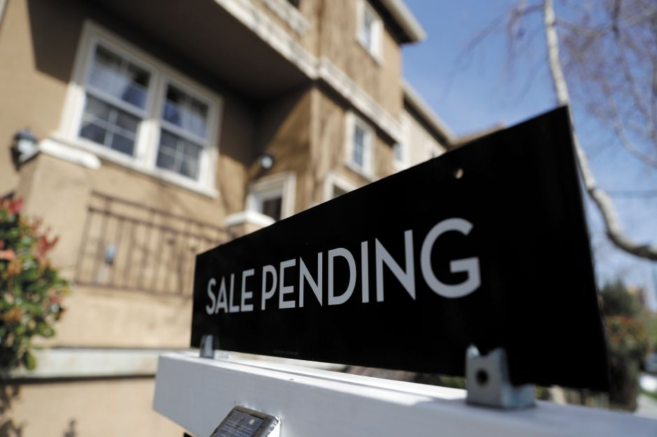 FILE - In this March 6, 2018, photo a sign advertises the pending sale of a home in San Jose, Calif. Economists expect that sales of previously occupied U.S. homes edged higher in June. (AP Photo/Marcio Jose Sanchez, File)