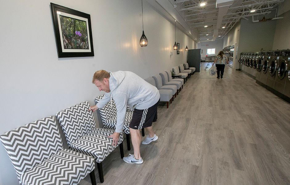 Chris Wilson, owner of Ultra Coin 2 Laundromat, straightens up  chairs at the new business.