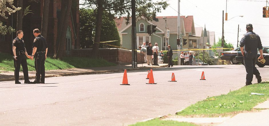 RJ file photo - Cones mark the shooting scene on Lewis Avenue as police Lt. Robert Green talks with another officer, May 10, 1999.