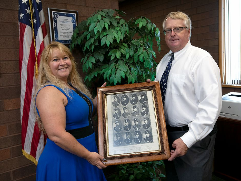Chief Jeffry Cossette and Sheri DeLuca hold a 113-year-old framed photograph of police department members donated by DeLuca in Cossette