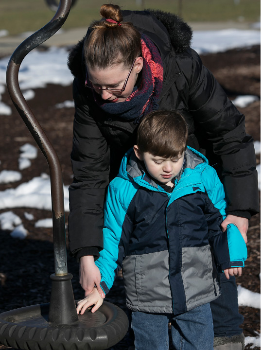 Jennifer Reilly, of Wallingford, helps son Collin, 7, feel textures at the playscape at Doolittle Park in Wallingford, Thursday, March 23, 2017. Collin became permanently blind at six months old after doctors performed surgery to remove cancer tissue from his brain, which they warned could happen prior to surgery. A fundraiser for Collin is being held at Serenity Salon and Day Spa, 118 Center Street, this Sunday from 10 a.m. to 3 pm. | Dave Zajac, Record-Journal