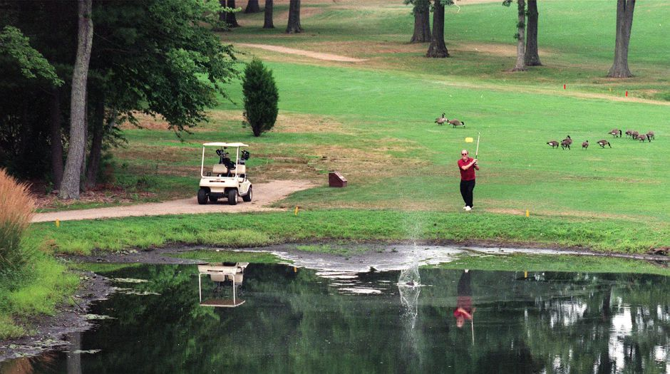 Tony Duso, of Bristol, watches as his second ball lands in the water on the 14th hole of Pine Valley Golf Course Tues., Aug. 10, 1999. The first one landed in the mud caused by the receding water during the drought.