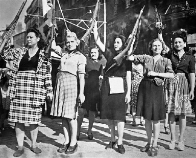 Women Maquis, raising rifles they used to fight the German garrison in Marseille, France on Sept. 10, 1944, before entry of Allied troops, parade with other residents (background) to celebrate their victory. (AP Photo)