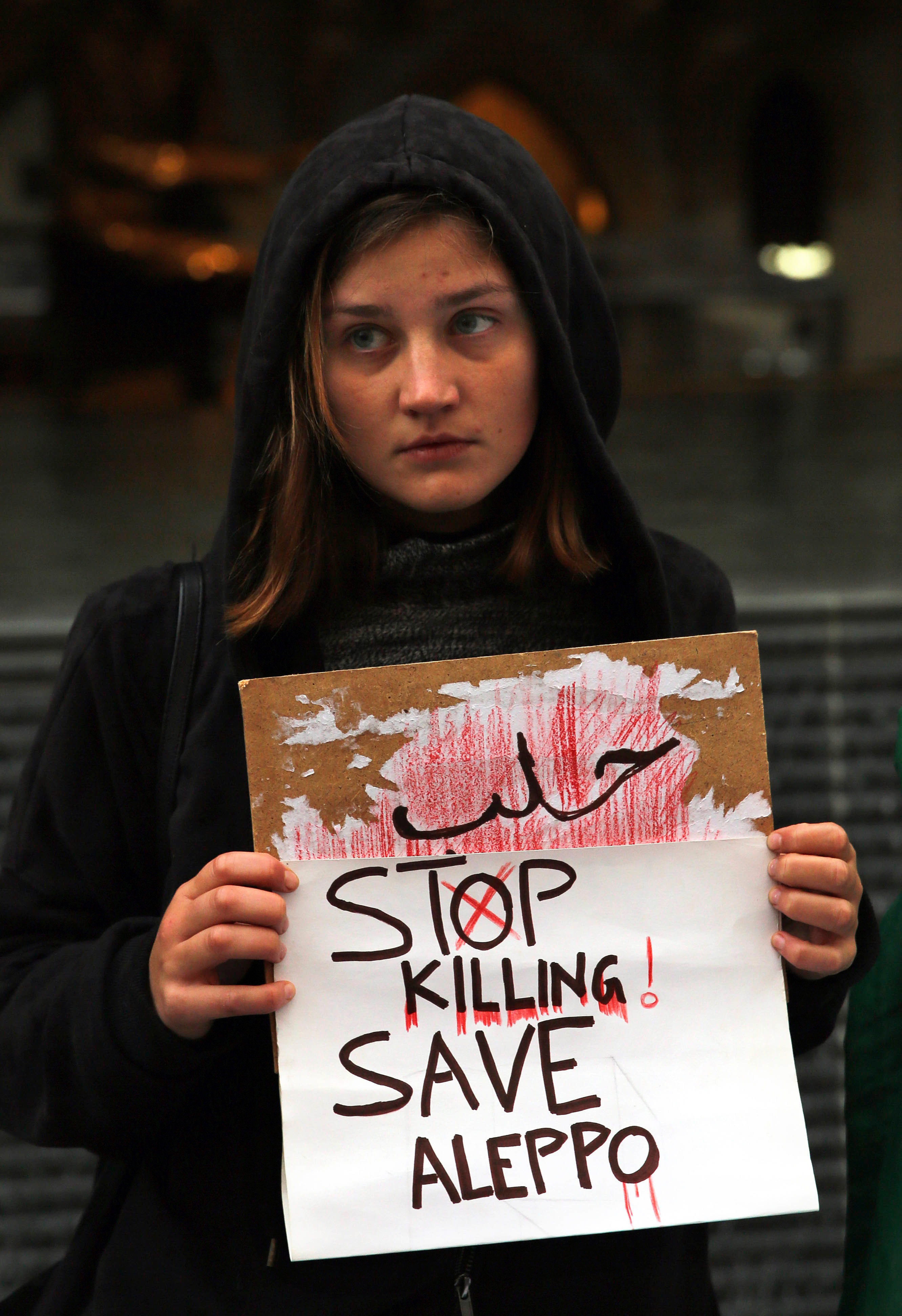 A Lebanese woman holds a placard, during a sit-in to express solidarity with residents of the Syrian city of Aleppo, in downtown Beirut, Lebanon, Tuesday, Dec. 13, 2016. The UN Security Council has scheduled an emergency meeting on the attacks in eastern Aleppo, where Syrian government forces appear poised to take the last rebel holdouts. (AP Photo/Bilal Hussein)