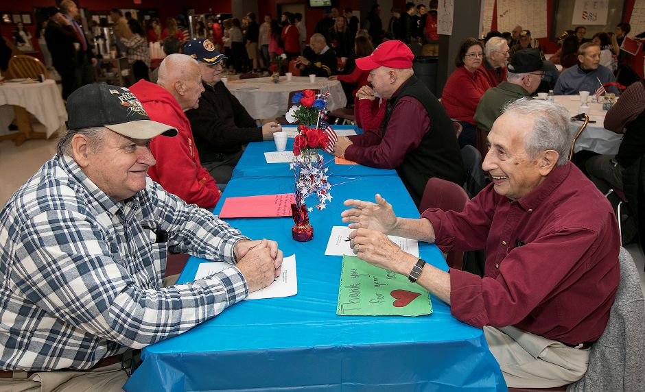 Veterans Curtis A. Genest, of Cheshire, left, and Andrew Madrigale, right, confer during a Veterans Day Celebration at Cheshire High School, Friday, Nov. 10, 2017. | Dave Zajac, Record-Journal