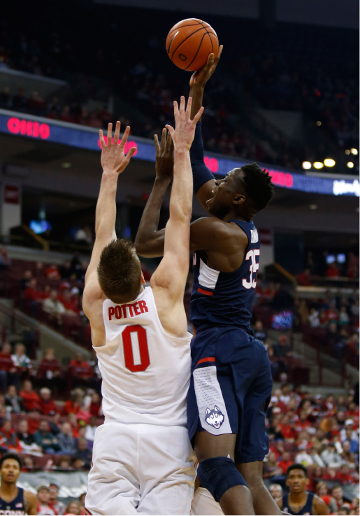 Connecticut center Amida Brimah, right, shoots against Ohio State center Micah Potter during the first half of an NCAA college basketball game in Columbus, Ohio, Saturday, Dec. 10, 2016. (AP Photo/Paul Vernon)