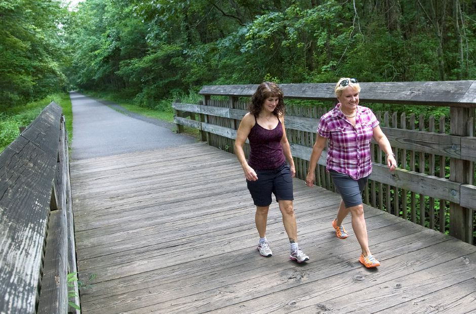 Marjorie Seggerman, left, and Beth Ferguson, of Cheshire, enjoy a walk on the Cheshire Linear Trail near Cornwall Ave. in Cheshire, Monday, July 6, 2015. A 69-year old woman claims she was knocked down by a track team runner on the linear trail and is asking that the town keep large groups off the trail. | Dave Zajac / Record-Journal