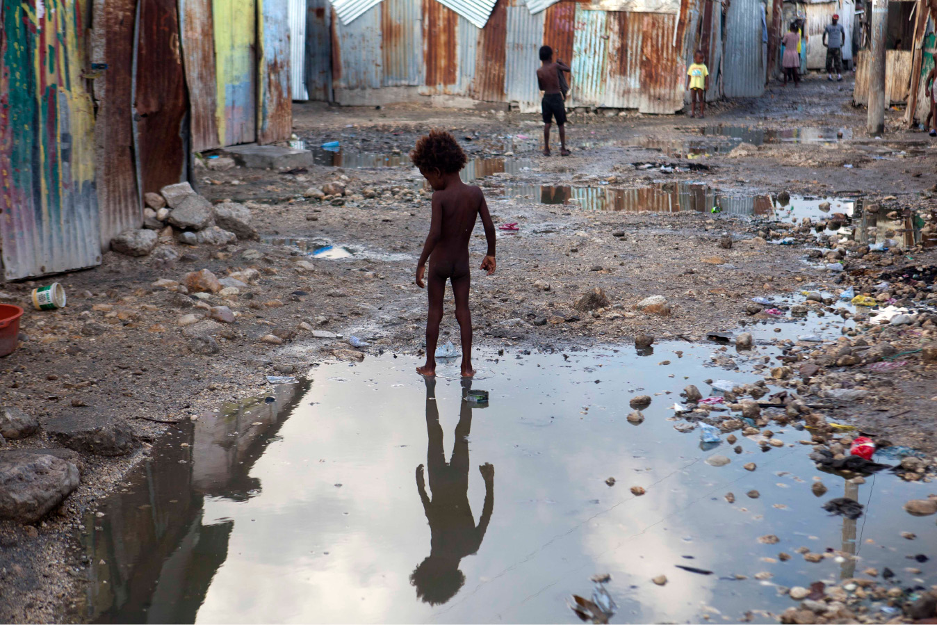A child plays in a puddle in the seaside slum of Port-au-Prince, Haiti, Wednesday, Sept. 6, 2017. Heavy rain and 185-mph winds lashed the Virgin Islands and Puerto Rico