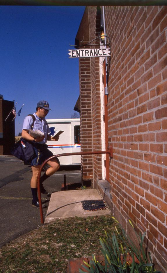 RJ file photo - Roy Graziano, a letter carrier for the Meriden post Office, delivers mail to the Main Street Baptist Church on Crown Street March 23, 1994.