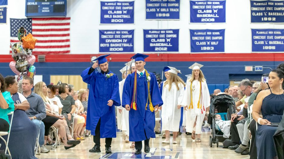 Graduating members of the Plainville High School band return to their seats after performing during the school