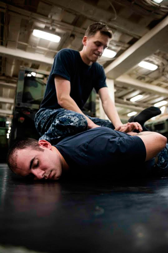 Cryptologic Technician 3rd Class Kyle Erland, from Wallingford, practices a Marine Corps Martial Arts Programholding technique on Cryptologic Technician 2nd Class Cody Donovan, from Lisbon Falls, Maine, aboard the amphibious transport dock ship USS Green Bay. | Mass Communication Specialist 1st Class Chris Williamson