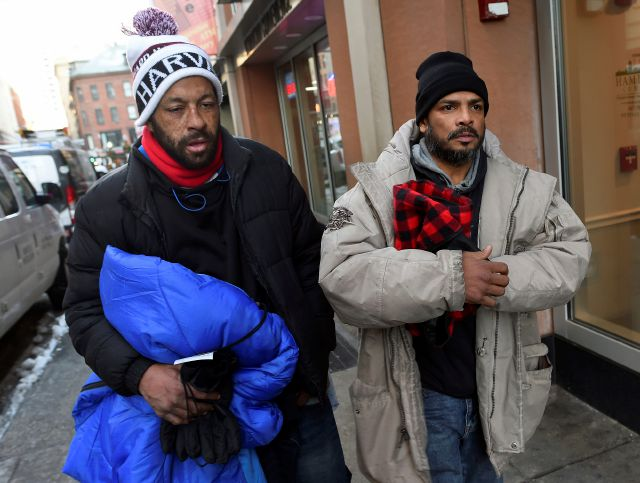FILE – In this Wednesday, Dec. 27, 2017, photo, homeless men Sean Stuart, left, and Segundo Rivera walk on a street after spending the day at St. Francis House in Boston. With temperatures across Massachusetts not expected to rise above freezing for days, politicians and advocates for the homeless are particularly concerned about getting as many people as possible into shelters. Stuart and Rivera told the Boston Herald that they