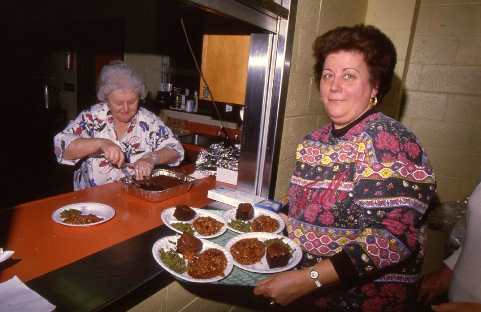 RJ file photo - Holy Angels Church Volunteer Helen Speltz cuts pieces of cake to add to lunches to be served by Ruth Kupfer at the Meriden Soup Kitchen at teh Salvation Army Jan. 24, 1994.