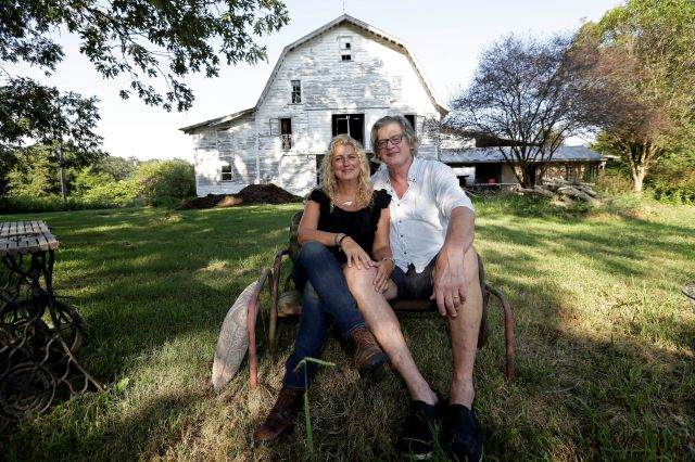 Heather and Tom LaGarde relax in the yard of their home near Saxapahaw, N.C., on Wednesday, Aug. 29, 2018. At first, the ramshackle North Carolina farm they spotted online in 2002 was only an occasional getaway from their home in Manhattan