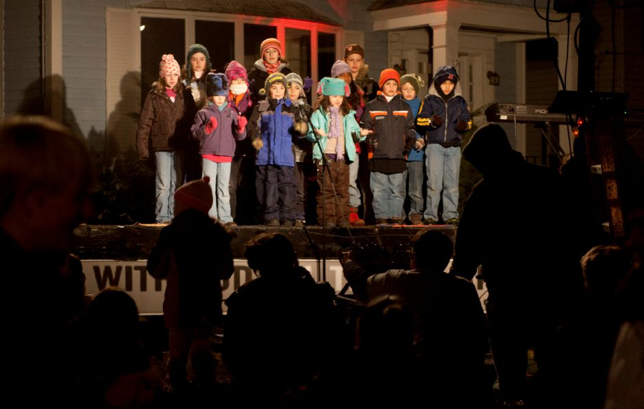 Children sing Christmas carols from the stage next to Faith Living Church in Planstville during the annual Christmas in the Village event Thursday night, Dec. 6, 2012. (Christopher Zajac / Record-Journal)