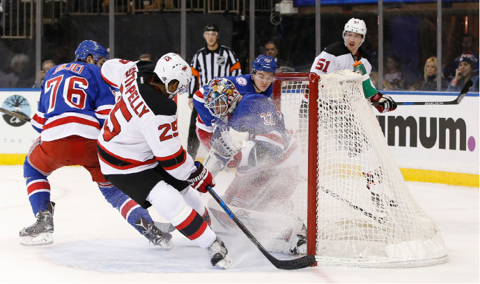 New York Rangers goalie Antti Raanta (32), of Finland, makes a save as New Jersey Devils right wing Devante Smith-Pelly (25) skates into the crease with Rangers defenseman Brady Skjei (76) defending during the first period of an NHL hockey game in New York, Sunday, Dec. 11, 2016. (AP Photo/Kathy Willens)