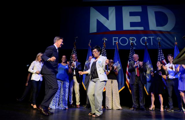 Connecticut gubernatorial candidate Ned Lamont, left, dances with New Haven Mayor Toni Harp as he celebrates his win in the Democratic primary in New Haven, Conn., Tuesday, Aug. 14, 2018. (AP Photo/Jessica Hill)