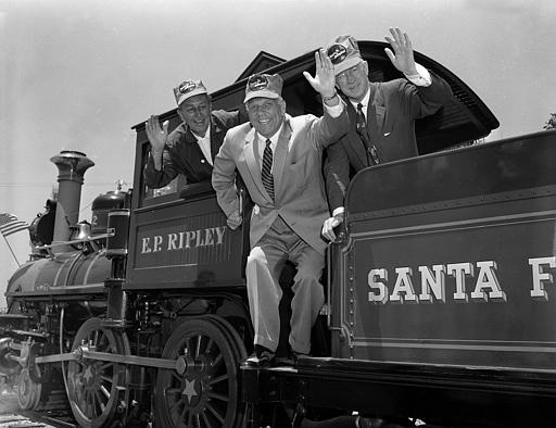 Governor Goodwin J. Knight, of California, center, Walt Disney, left, and Fred G. Gurley, President of Santa Fe Railroad, right, board the cab of an old-time railroad engine to take a ride around Disneyland in Anaheim, Calif. July 17, 1955. Disneyland, 160 acres and 17 million dollars of fun opened its doors today. (AP Photo)