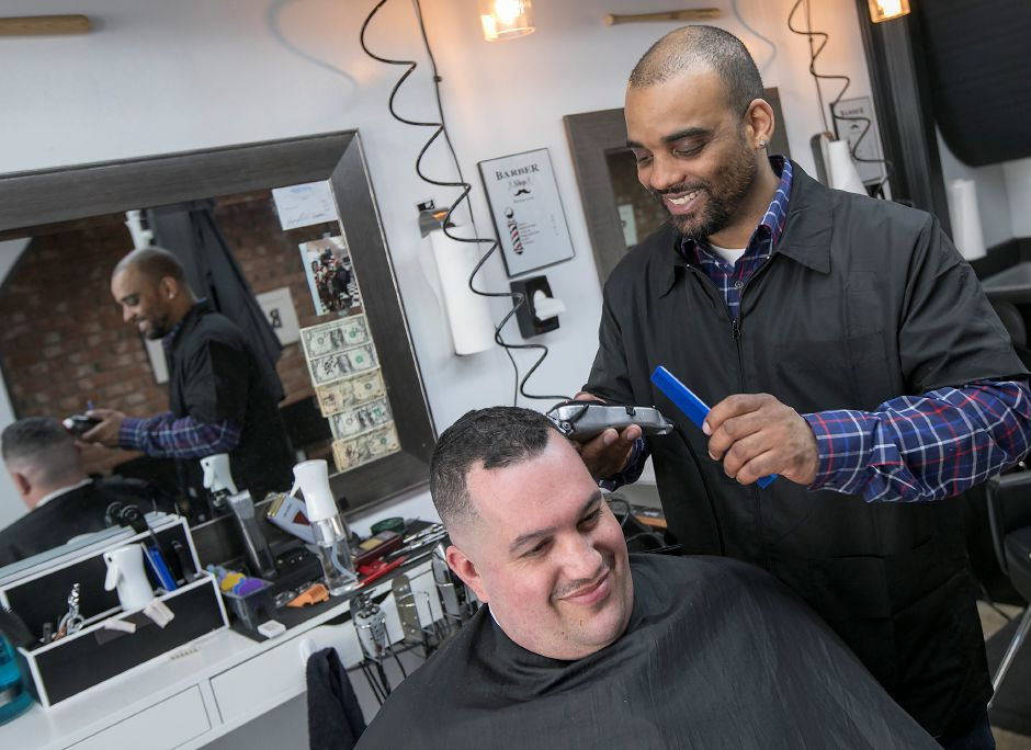 Barber Trey Maestri, owner of Trey's Barbershop, gives a trim to Bryan Sola, of Southington, at the new business on Center Street in Southington. Dave Zajac, Record-Journal