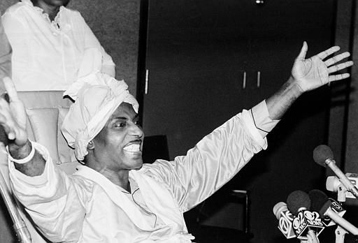Rock and roll entertainer Little Richard holds his arms out as he greets reporters during a news conference in a hospital in Los Angeles, Ca., Friday, Oct. 25, 1985.  Richard thanked God for saving his life.  Doctors said the 52-year-old singer is lucky to survive an automobile accident Oct. 8.  (AP Photo/Nick Ut)