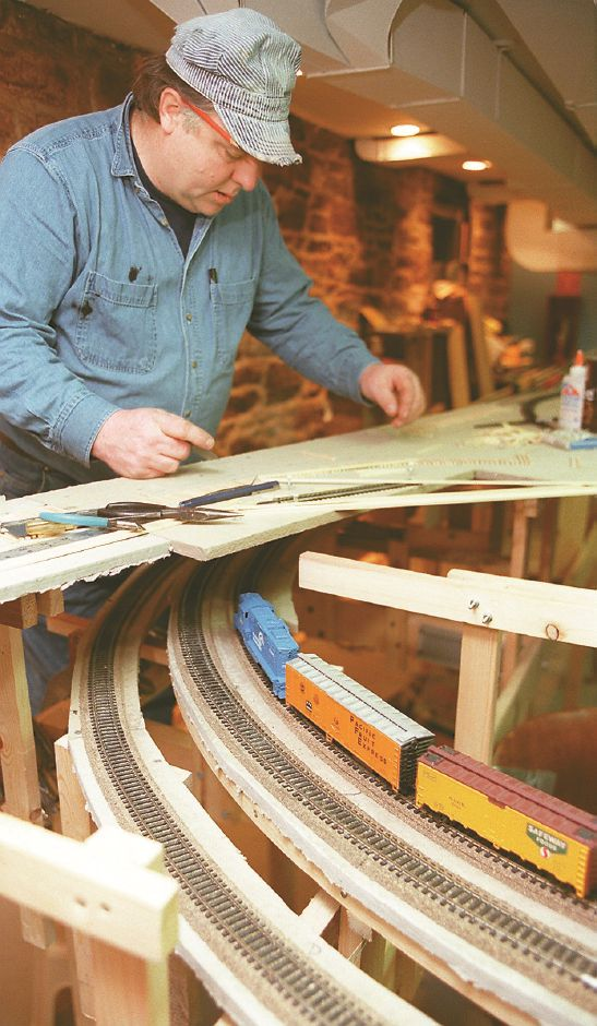 RJ file photo - Bob Winnie Jr., glues small wooden ties onto a model train bed at the Wallingford Train Station as a H-O model train passes by him. He and a group of other model train enthusiasts are members of the New Haven Society of Model Engineers, Inc. August 1998.