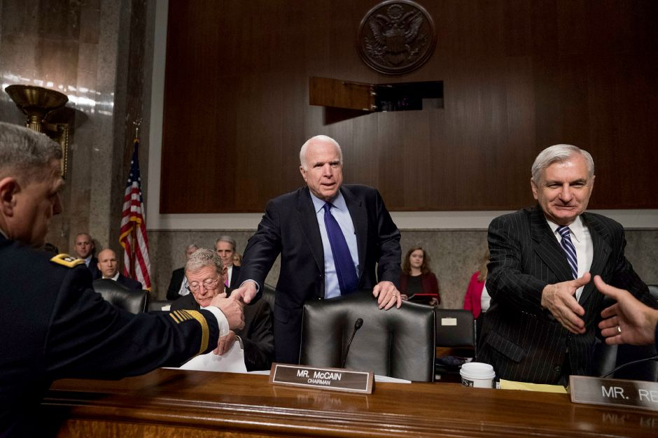 Senate Armed Services Committee Chairman Sen. John McCain, R-Ariz., center, accompanied by the committee