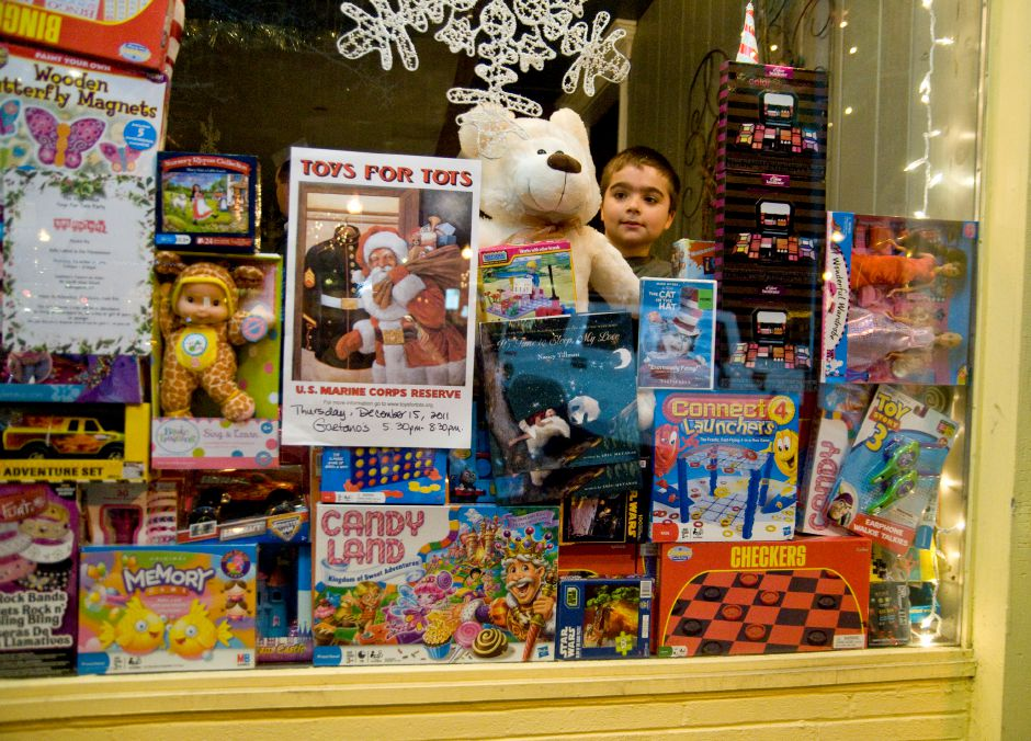 Wallingford resident Michael Dallaripa,11, stacks a teddy bear in the front window of Gaetano