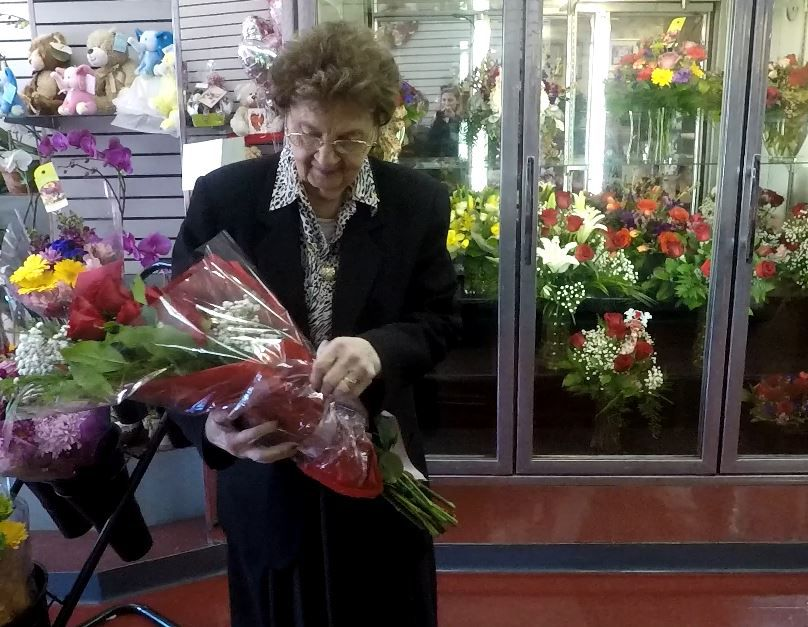 Ann Greco holds a rose bouquet at her family business.