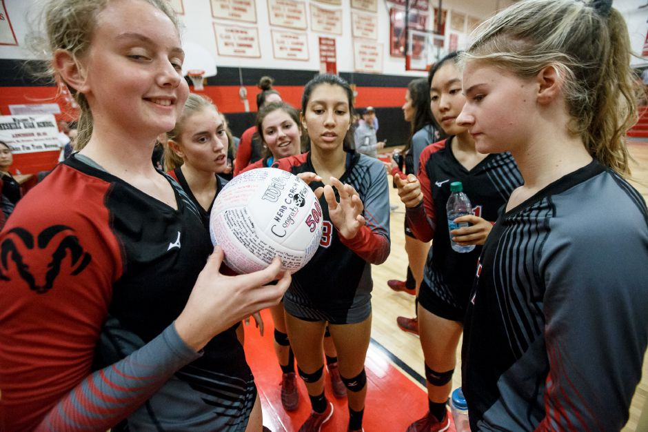 Cheshire volleyball team members sign a ball to celebrate head coach Sue Bavone