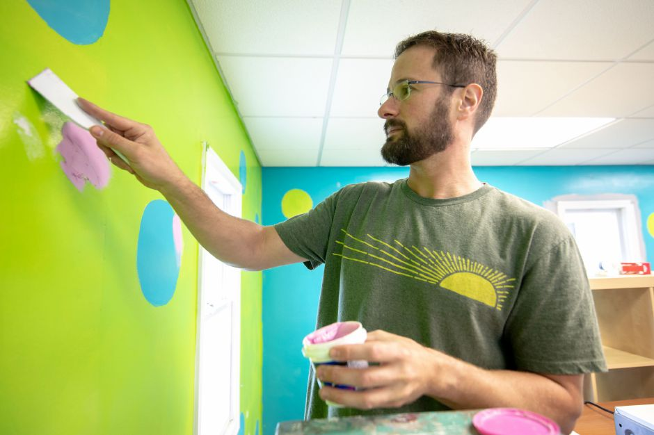 Carlos Teixeria, salesperson for Behr, repaints the walls of one of the buildings at Lisa Inc.
