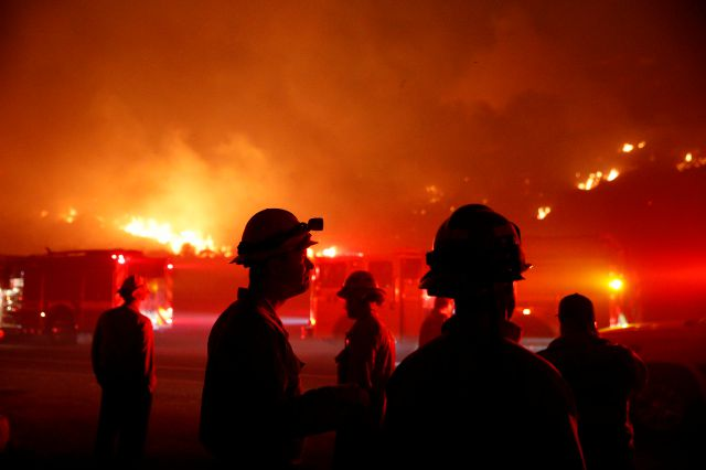 Firefighters gather in front of a residential area as a wildfire burns along the 101 Freeway Tuesday, Dec. 5, 2017, in Ventura, Calif. Raked by ferocious Santa Ana winds, explosive wildfires northwest of Los Angeles and in the city