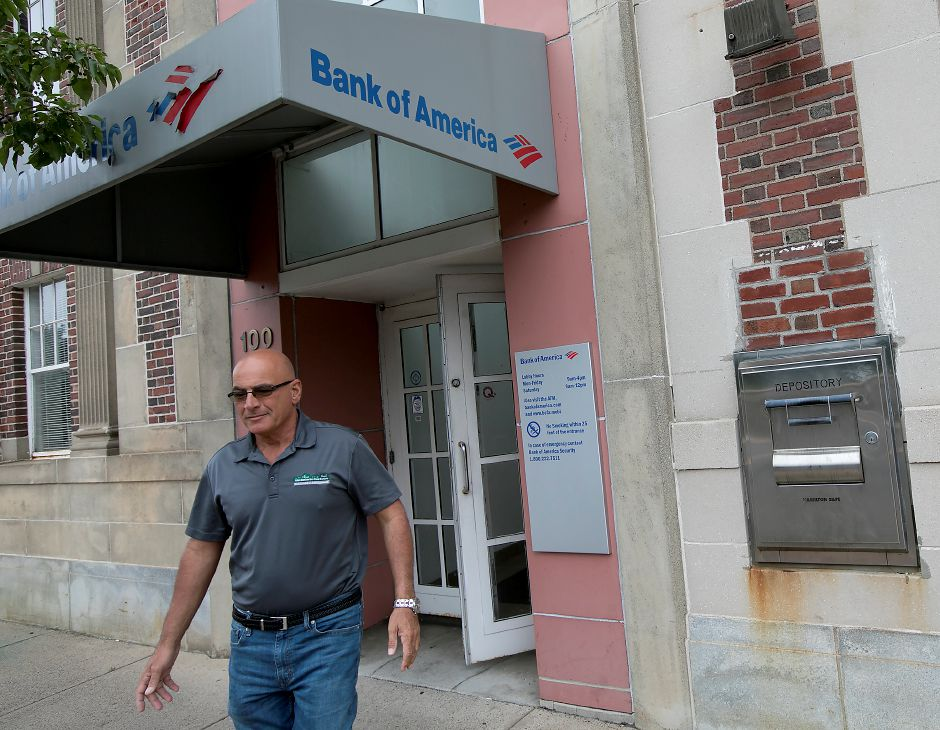 Longtime customer Alan Barberino, of Wallingford, walks out of the Bank of America branch at 100 Center St. in Wallingford on Wednesday. The branch will close later this year, officials said Wednesday. Dave Zajac, Record-Journal